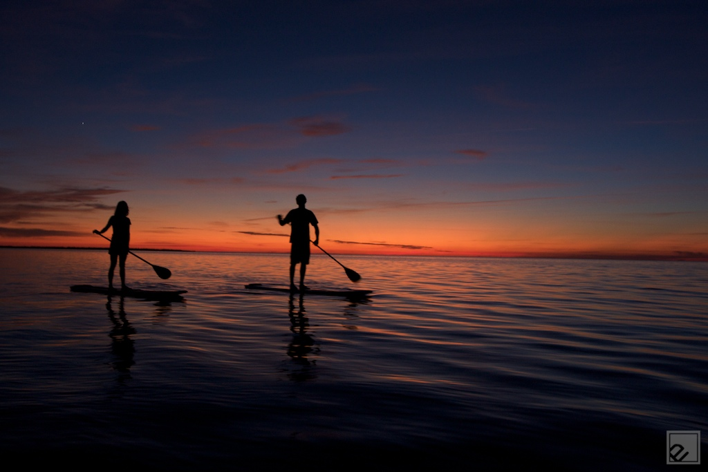 A couple standup paddles through a sunset on the pamlico Sound