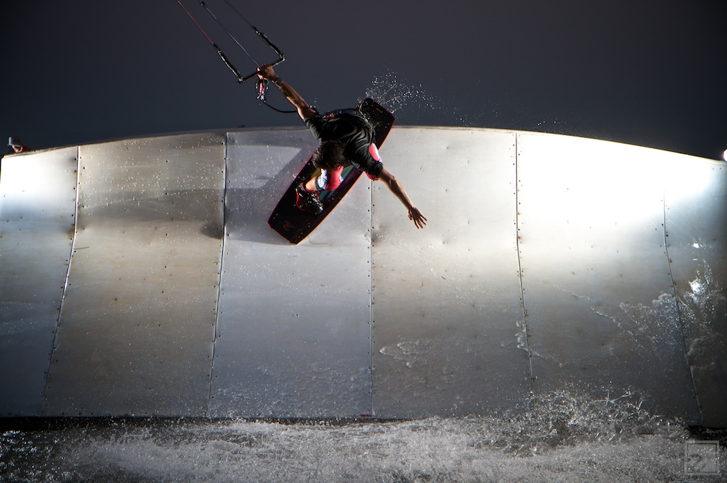 a kiteboarder does a trick on a wallride obstical in cape hatteras nc