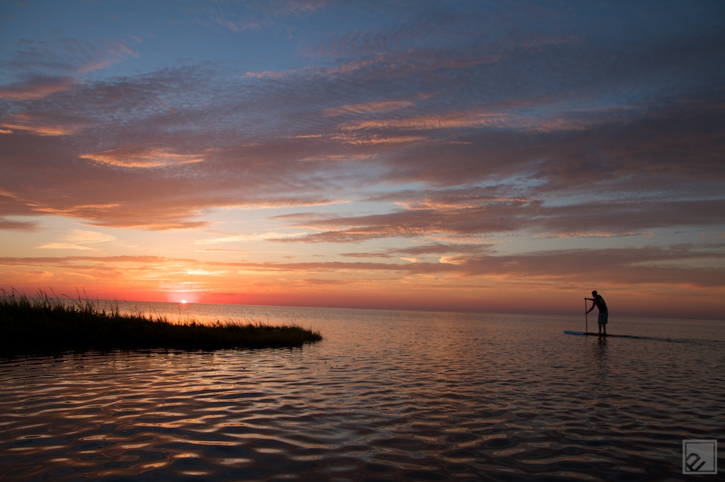 a standup paddleboarder paddles twords a sunset in cape hatteras nc