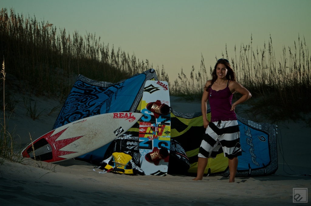 a girl kiteboarder shows off her gear