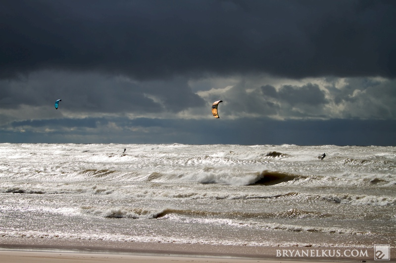 2 kiteboarders riding in waves with stormy skies on Lake Michigan