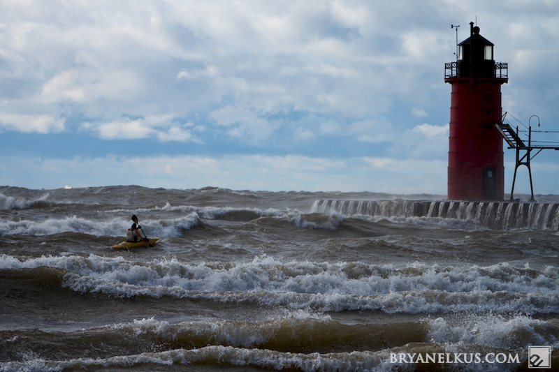 a kyaker paddles in front of the south haven pier in rough waters