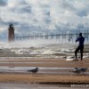 a sufer prepairs for a paddle in lake michigan by the south haven lighthouse