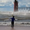 a surfer walks twords lake michigan and the rough waters by the south haven lighthouse