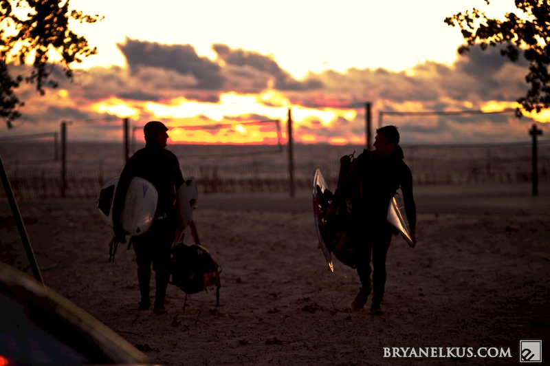 two kiteboarders walk back from a glowing sunset of the shore of lake michigan.