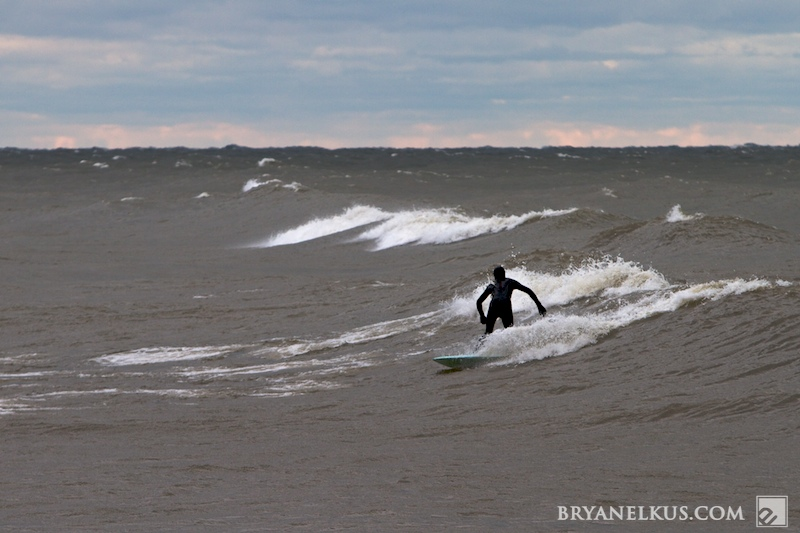 a surfer rides a wave on lake michigan