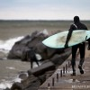 a lake michigan surfer walks out on the pier