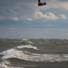 a kiteboarder jumps high over lake michigan on a stormy day
