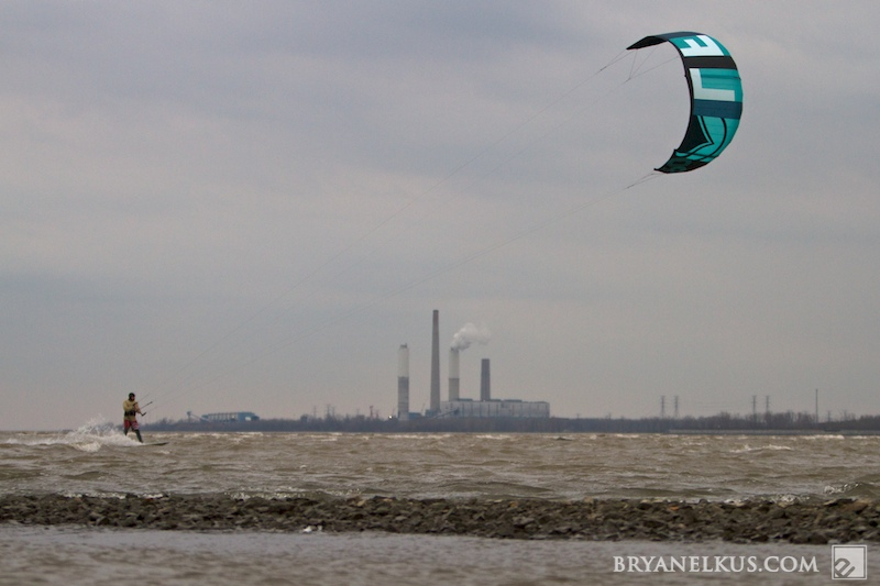 A Kiteboarder riding in Lake Erie Michigan with a power plant in the background