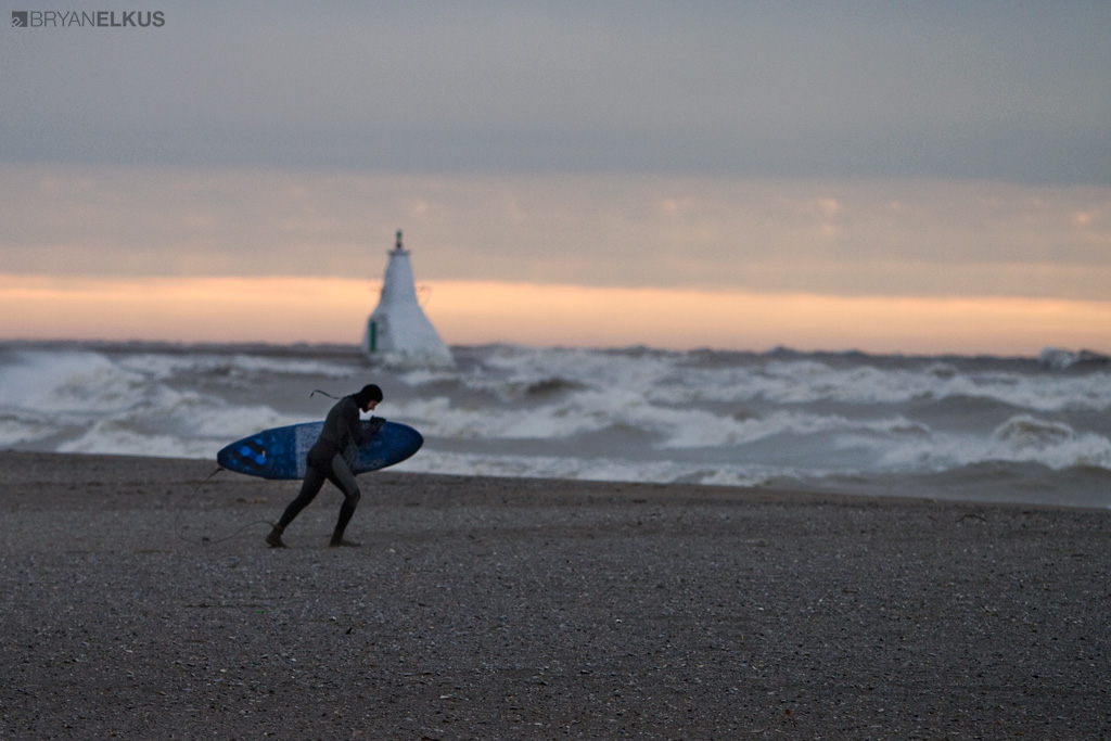 a surfer walks on the beach in Erieau Canada during a stormy day on Lake Erie