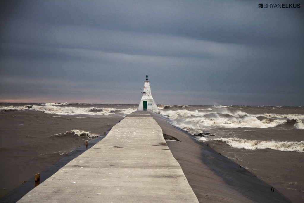 a view of waves crashing next to the Erieau lighthouse