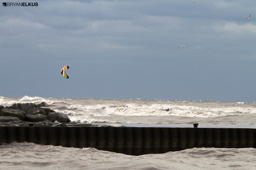 a kiteboarder rides waves on lake eire